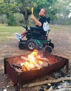 Wheelchair user enjoying a campfire at a campsite