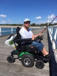 Wheelchair user fishing off a pier